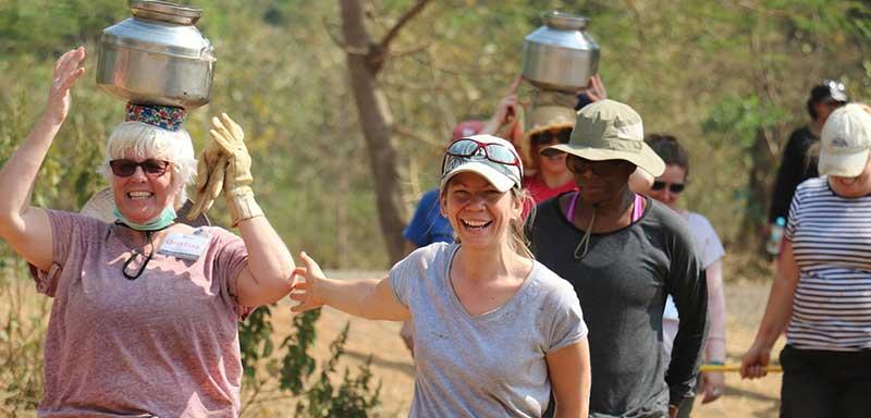 women carrying water in india volunteers