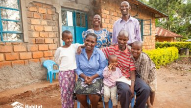 a beneficiary family sat in front of their new home