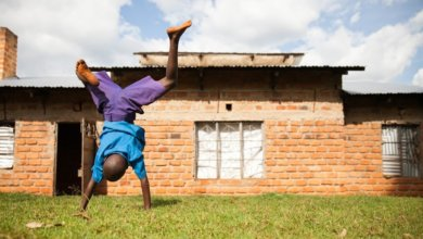 child playing in front of house in kenya
