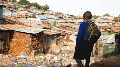 boy walking through slums