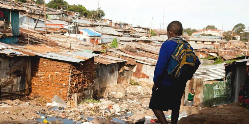 boy walking through slums