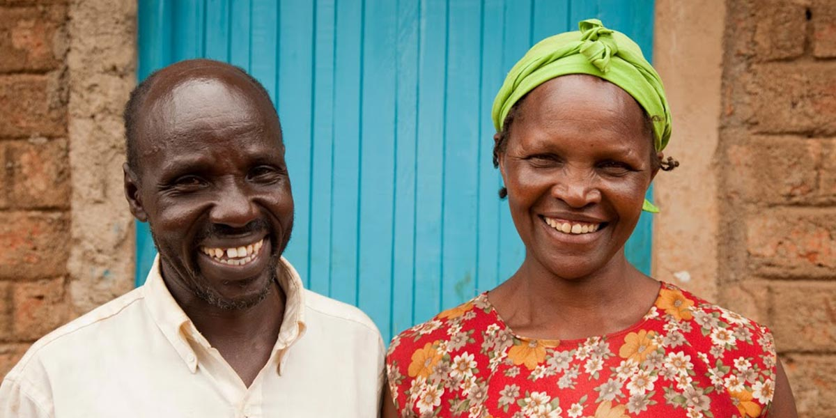 a couple smiling outside their own home